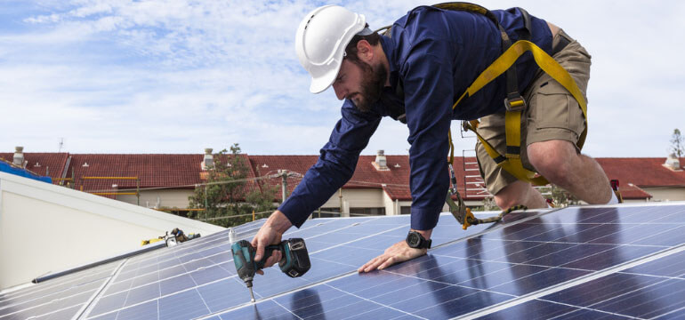 Technician Installing a Solar Panel System on the Roof of a House